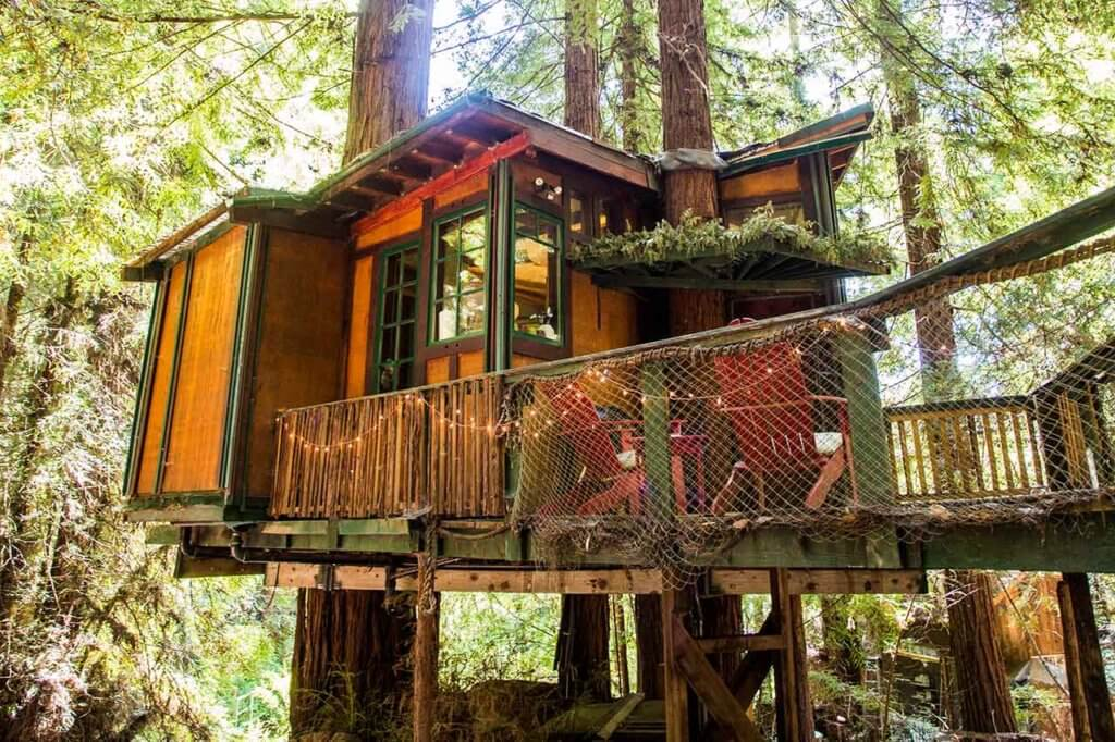 drive-swim-fly-santa-cruz-mountains-treehouse-hotel-outside-view-sun-through-trees-hanging-bridge-header